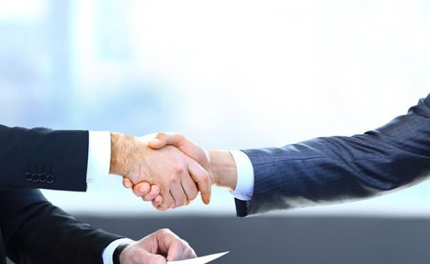 owner of a small business in Alexandria, VA shaking hands with the owner of an HR services firm to discuss good HR practice