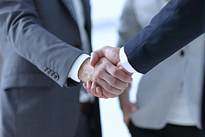 a former employee of a company shaking hands with the owner of an HR solutions firm after the employee agreed to work for his former company again in the future