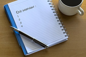 a notepad with exit interview questions that an HR solutions firm will ask to an employee who is moving on