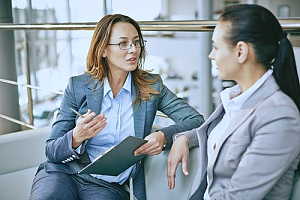 an employee of an HR outsourcing solutions firm holding an exit interview with one of her clients' employees to benefit both the company and the former employee