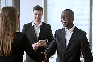 an excited HR outsourcing firm professional shaking hands with a business woman as they prepare to discuss HR outsourcing solutions and their benefits