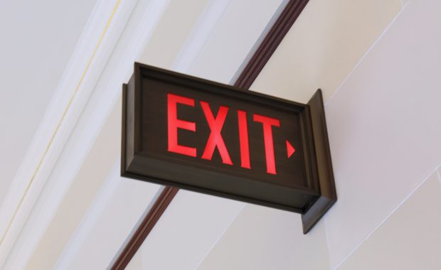 an exit sign above a door to represent an employee exit interview