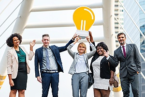 a group of coworkers holding a lightbulb after receiving executive coaching and training