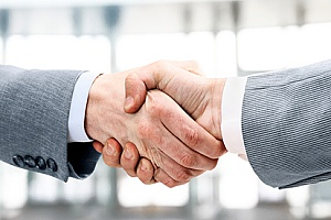 a new employee shaking hands with a business owner who has received assistance with talent acquisition from an HR solutions firm