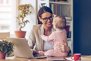 a mother working at her desk with her baby daughter