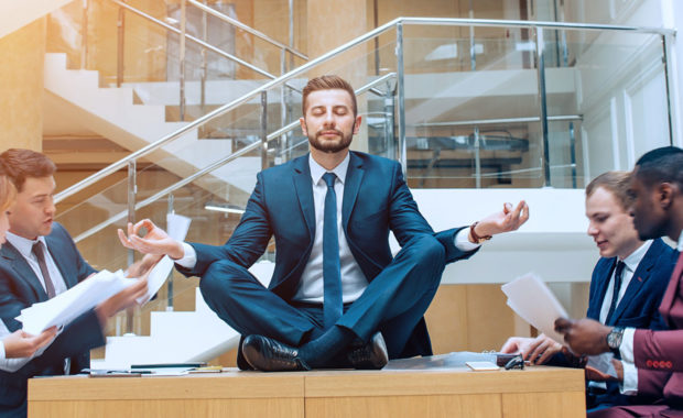 a business man meditating and focusing on employee wellness