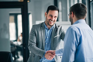 a direct hire shaking hands with the outsourced HR consultant that helped him become hired