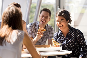 employees enjoying each other and eating pizza