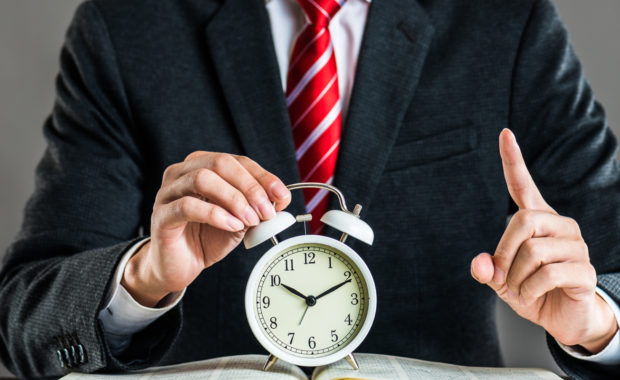 HR consultant standing behind a clock explain the new overtime rule