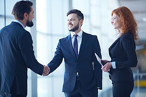 a human resource professional shaking hands with a small business owner