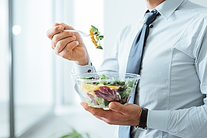 business employee eating a healthy salad in the office