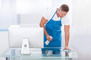 Employee wiping down desk