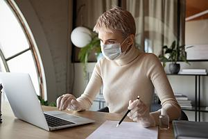 Employee on laptop with mask and gloves