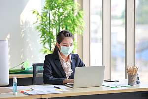 Woman at desk in office with mask on
