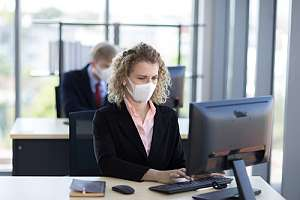 Woman sitting at work desk with mask