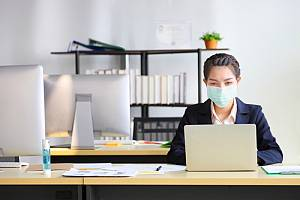 Masked employee in office at desk