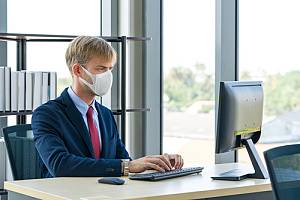 Employee in mask on computer