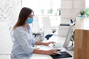 Masked employee in office