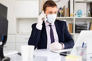 Masked employee on phone in office