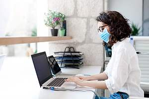 Masked employee working at desk