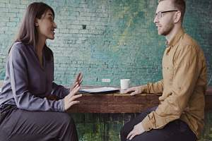 Two people on stools talking
