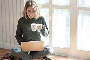 Employee sitting on ground in home with tea