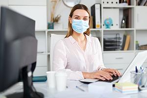 Employee at desk working in mask