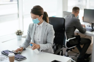 business women at her desk disinfecting it wearing a mask
