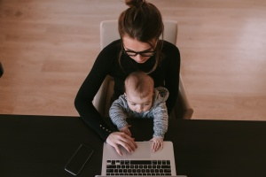 mom working at her computer while her kid sits on her lap