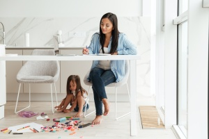 mom working from home and her kid playing under the table