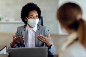 women talking to her co worker wearing a mask
