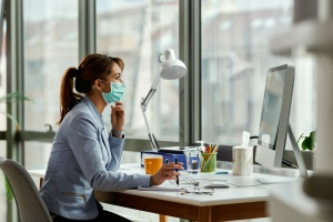 women at desk thinking about Workplace Vaccination Mandates